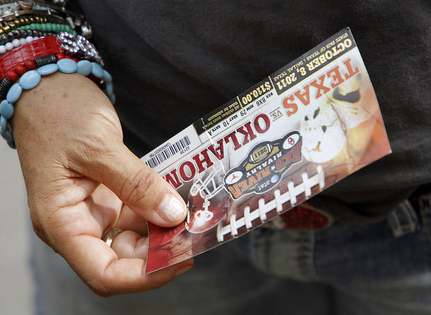An Oklahoma fan holds their ticket during the Red River Rivalry college football game between the University of Oklahoma Sooners (OU) and the University of Texas Longhorns (UT) at the Cotton Bowl in Dallas, Saturday, Oct. 8, 2011. Photo by Chris Landsberger, The Oklahoman  ORG XMIT: KOD