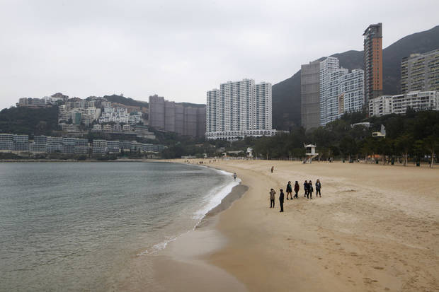 In this Jan. 15, 2013 photo, visitors walk on the Repulse Bay Beach in Hong Kong. If you visit Hong Kong at any time except the winter, you'll likely encounter sweltering weather. To cool down, head to one of the many beaches. Hong Kong Island has a few, including Big Wave Bay in Shek O or the beach at tony Repulse Bay, but they do get crowded on weekends. (AP Photo/Kin Cheung)