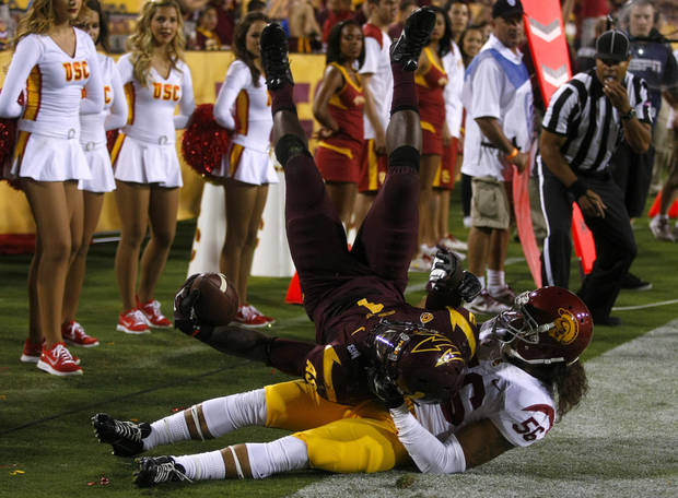Arizona State running back Marion Grice (1) scores a touchdown over Southern California linebacker Anthony Sarao (56) during the first half of an NCAA college football game on Saturday, Sept. 28 2013, in Tempe, Ariz. (AP Photo/Rick Scuteri)