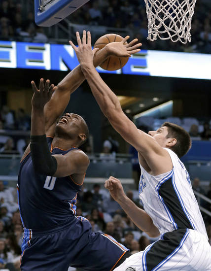 Orlando Magic's Nikola Vucevic, right, of Montenegro, fouls Charlotte Bobcats' Bismack Biyombo (0) as Vucevic tries to block a shot during the first half of an NBA basketball game, Friday, Jan. 18, 2013, in Orlando, Fla. (AP Photo/John Raoux)