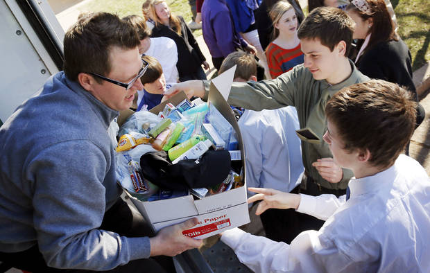 Mount St. Mary boys basketball coach Andy Fisher collects donations from his players Friday at Sacred Heart Catholic Church, 2706 S Shartel, in Oklahoma City. Players from the teams participating in the Hoops 4 Hope tournament loaded items they donated to Catholic Charities into a truck after having Mass to start the event.  Photo by Nate Billings, The Oklahoman <strong>NATE BILLINGS</strong>
