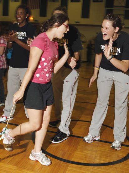 Special Olympics athlete Paige Henderson gets a high-five from Oklahoma women's basketball player Whitney Hand during a pep assembly at Longfellow Middle School in May 2010. PHOTO BY STEVE SISNEY, The Oklahoman Archives