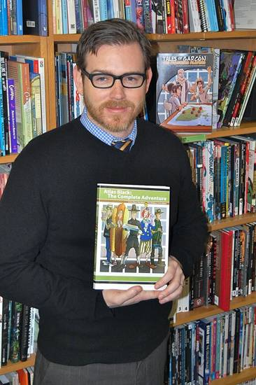 "OU professor Jeremy Short is seen with his graphic novel ""Atlas Black: The Complete Adventures."" Photo by Annette Price, for The Oklahoman"