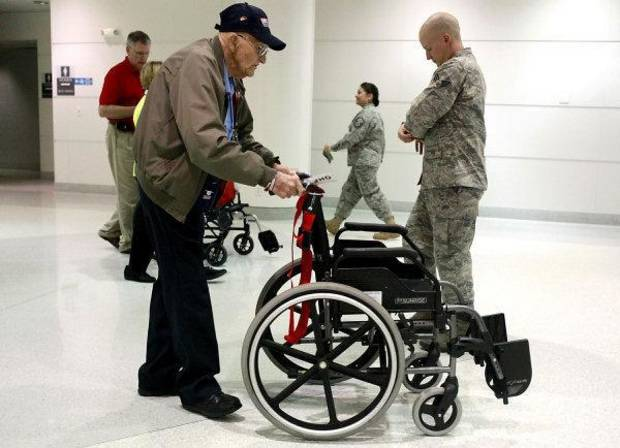 Veteran James Criger, of Grove, Okla., pushes a wheelchair past Adam Milligan, a current member of the Air Force from Broken Arrow Oklahoma in the terminal at Baltimore Washington International Airport in Baltimore, Maryland on Wednesday, Oct. 12, 2011. Criger was on his way home from an Honor Flight visit to the WWII Memorial and other monuments in Washington, Milligan boarded a plane to go overseas. Photo by John Clanton, The Oklahoman ORG XMIT: KOD
