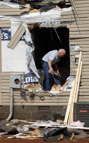 A man tosses out damaged debris from a house on Yarbrough Road after a severe weather passed the area on   Friday morning March 2, 2012 in Huntsville, Ala.  A reported tornado destroyed several houses in northern Alabama as storms threatened more twisters across the region Friday (AP Photo/The Huntsville Times, Eric Schultz)  ORG XMIT: ALHUT112