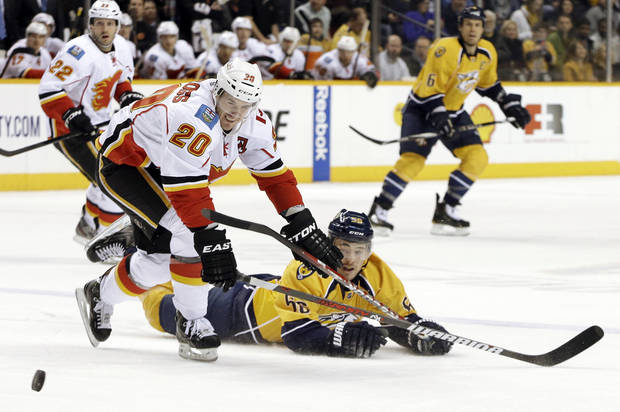 Calgary Flames left wing Curtis Glencross (20) and Nashville Predators defenseman Roman Josi (59), of Switzerland, chase the puck in the second period of an NHL hockey game, Thursday, March 21, 2013, in Nashville, Tenn. (AP Photo/Mark Humphrey)