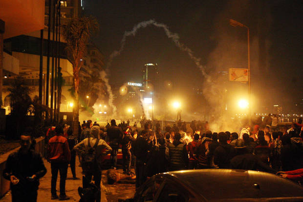In this Saturday, Jan. 26, 2013 photo, demonstrators throw stones at security forces who respond with tear gas in front of international hotels along the Nile in downtown Cairo, Egypt. Unrest surrounding the second anniversary of Egypt&#039;s revolution broke out in Cairo and other cities for a third day, with protesters clashing for hours with riot police who fired tear gas that encompassed swaths of the capital&#039;s downtown. (AP Photo/Mohammed Abu Zaid)