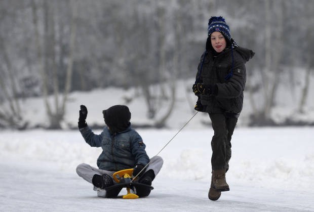 Children play on a frozen pond in Aalter, 75 kilometers (47 miles) west of Brussels, Wednesday, Jan. 23, 2013. Belgium has been in the grip of cold and snowy weather for a week. (AP Photo/Yves Logghe)