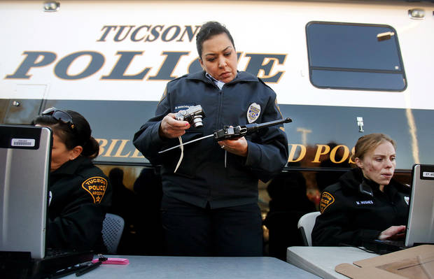 Officer Monica Vannorman, center, photographs a pistol as Officer Merri Hughes, right, logs relinquished weapons at a gun buyback event on Tuesday, Jan. 8, 2013, at the Tucson Police Department Midtown Substation in Tucson, Ariz. Gun owners relinquished their handguns and rifles in exchange for a $50 Safeway gift card on Tuesday, which marked the second anniversary of the shootings in Tucson that left six dead and 13 injured, including former Rep. Gabrielle Giffords.  (AP Photo/Arizona Daily Star, Mike Christy)  ALL LOCAL TV OUT; PAC-12 OUT; MANDATORY CREDIT; NO SALES; MAGS OUT