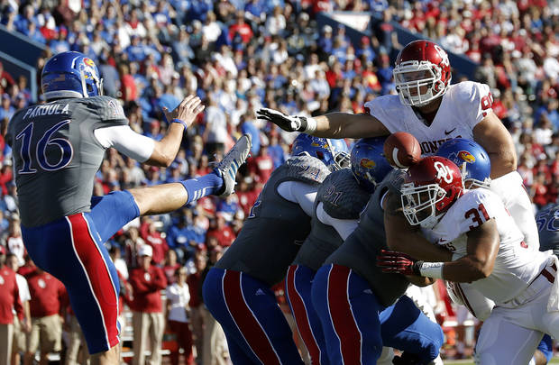 Oklahoma's Matt Dimon (90) and Londell Taylor (31) leap to block a Kansas punt for a safety during the college football game between the University of Oklahoma Sooners (OU) and the University of Kansas Jayhawks (KU) at Memorial Stadium in Lawrence, Kan., Saturday, Oct. 19, 2013. Photo by Sarah Phipps, The Oklahoman