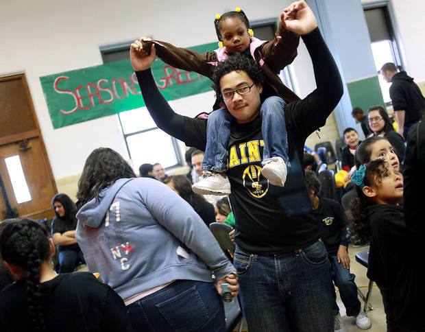 Nikko Taupule, a freshman at Santa Fe South High School, carries Xaria Smith, a kindergarten student, on his shoulders during the annual Christmas Party and gift exchange at Santa Fe South High School in OKlahoma City on Friday, Dec. 3, 2010. Photo by John Clanton, The Oklahoman