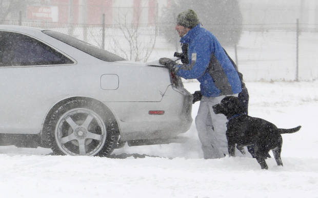 People try to move a car stuck in snow on Penn just south of I-44 during a winter storm in Oklahoma City, Tuesday, Feb. 1, 2011. Photo by Nate Billings, The Oklahoman 