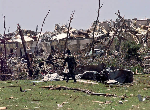 MAY 3, 1999 TORNADO: Tornado damage: A National Guard soldier walks through a field east of Sooner Road between I-40 and SE 15th Street Tuesday afternoon.  Motel in background was destroyed.