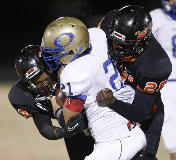 Oologah's John Vansingel is brought down by Douglass' Erik King, left, and Jas'Sen Stoner during a high school playoff football game in Oklahoma City, Friday, Nov. 19, 2010.  Photo by Bryan Terry, The Oklahoman