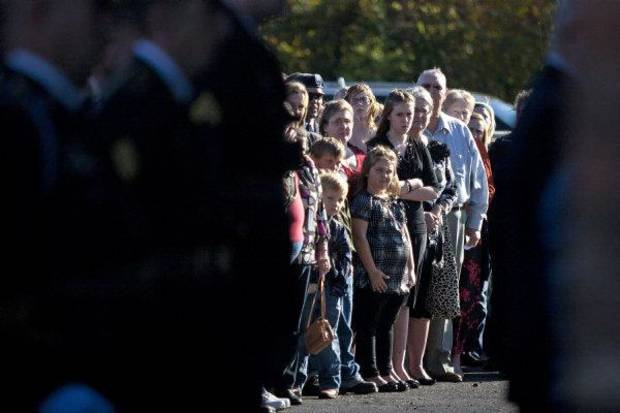 Family and friends of Spc. Sarina N. Butcher, 19, of Checotah, Okla., watch as National Guard Honor Guard members prepare to carry her casket out of the Brazzell/Cornish Funeral Home during a Friday, Nov. 11, 2011,  service in Prescott, Ark. Butcher is both the youngest  and first female Oklahoma National Guard member to die in combat in Iraq and Afghanistan during wartime. She died from wounds caused by an improvised explosive device on Nov. 1 while serving in Afghanistan.(AP Photo/ The Texarkana Gazette, Adam Sacasa)