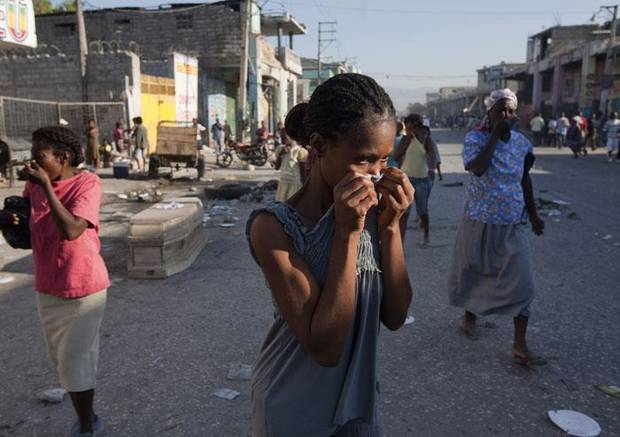 People cover their faces as they walk past a coffin at a street in Port-au-Prince, Friday, Jan. 15, 2010. A powerful earthquake hit Haiti Tuesday. (AP Photo/Ramon Espinosa)
