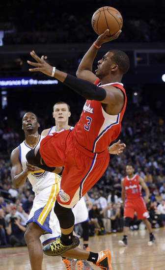 Los Angeles Clippers' Chris Paul (3) scores on an off-balance shot against the Golden State Warriors during the first half of an NBA basketball game in Oakland, Calif., Monday, Jan. 21, 2013. (AP Photo/Marcio Jose Sanchez)