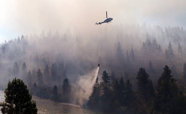 A helicopter drops water taken from the adjacent Yakima River onto a wildfire Tuesday, Aug. 14, 2012, on Highway 10 near Cle Elum, Wash. The fast-moving wildfire has burned 60 homes across nearly 40 square miles of central Washington grassland, timber and sagebrush. No injuries have been reported but more than 400 people have been forced to flee. AP photo