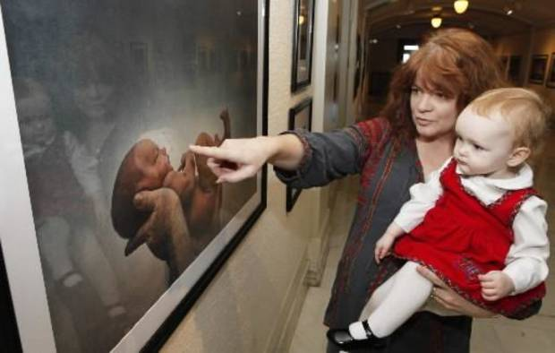 Brandy McDonnell's daughter Brenna, 21 months, and photographer M.J. Alexander look at Brenna's portrait that Alexander took when the girl was 100 hours old. It is displayed in the Capitol's North Gallery through April 15. (Photo by David McDaniel, The Oklahoman)
