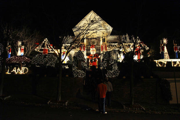 This Dec. 4, 2012 photo shows spectators viewing an elaborately decorated home for the holidays in the Brooklyn borough of New York. Each holiday season, tour operator Tony Muia takes tourists from around the world on his �Christmas Lights & Cannoli Tour� visiting the Brooklyn neighborhoods of Dyker Heights and Bay Ridge, where locals take pride in over-the-top holiday light displays. (AP Photo/Seth Wenig)
