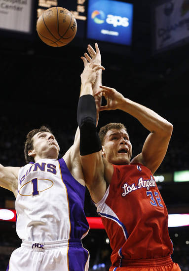 Phoenix Suns' Goran Dragic (1), of Slovenia, grabs a rebound away from Los Angeles Clippers' Blake Griffin (32) during the first half in an NBA basketball game on Thursday, Jan. 24, 2013, in Phoenix. (AP Photo/Ross D. Franklin)