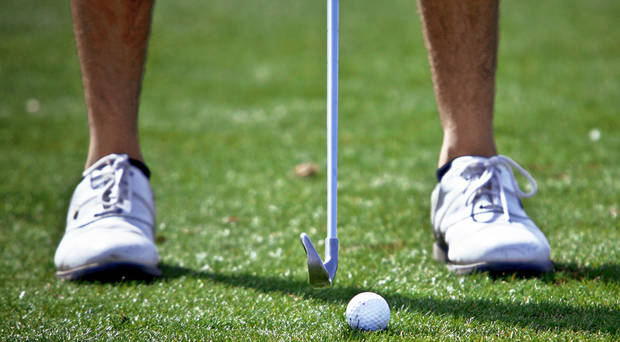 Left: A golfer lines up a shot during the Edmond Invitational Golf Tournament at KickingBird Golf Club.  PHOTO BY CHRIS LANDSBERGER, OKLAHOMAN ARCHIVE