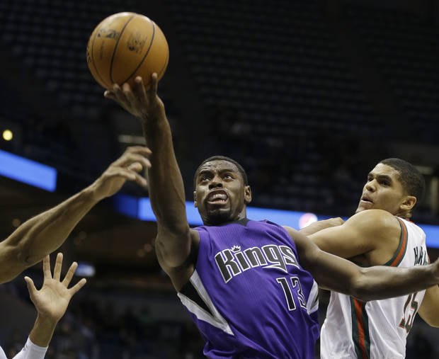 Sacramento Kings' Tyreke Evans (13) drives against Milwaukee Bucks' Tobias Harris, right, during the first half of an NBA basketball game on Wednesday, Dec. 12, 2012, in Milwaukee. (AP Photo/Jeffrey Phelps)