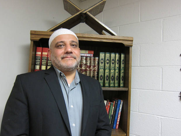 Imad Enchassi, imam of the Islamic Society of Greater Oklahoma City, stands near a bookshelf in his office at Oklahoma City University, where he is a professor. <strong>Carla Hinton - The Oklahoman</strong>