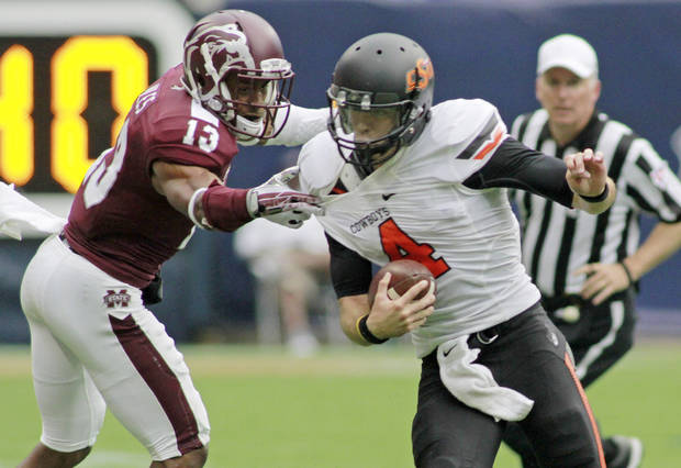 Oklahoma State quarterback J.W. Walsh (4) slips from the grasp of Mississippi State defensive back Cedric Jiles (13) for a gain of yardage on a quarterback-keeper during the second half in their NCAA college football game on Saturday, Aug. 31, 2013, in Houston. (AP Photo/Richard Carson)