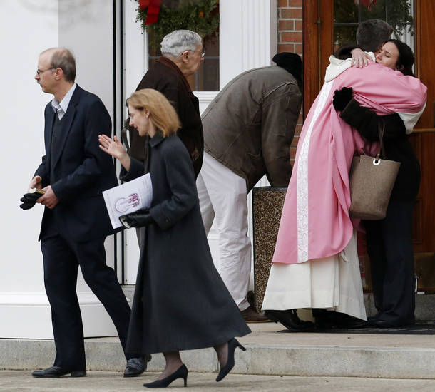 A priest embraces a woman outside St. Rose of Lima Roman Catholic Church between Masses, Sunday, Dec. 16, 2012, in Newtown, Conn. On Friday, a gunman allegedly killed his mother at their home and then opened fire inside the Sandy Hook Elementary School in Newtown, killing 26 people, including 20 children. (AP Photo/Julio Cortez)