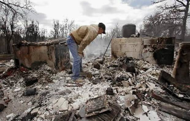 Kenneth  Wertz digs through the remains of his house of more than 40 years as he looks for a few salvageable remains from the house that was destroyed by wildfires on Friday, April 10, 2009, in Choctaw, Okla. Photo by Chris Landsberger