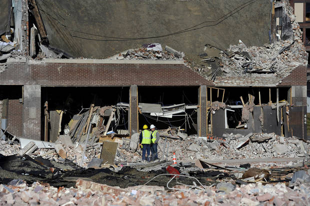   Inspectors stand in debris, Saturday, Nov. 24, 2012, at the site of a gas explosion that leveled a strip club in Springfield, Mass., on Friday evening. Investigators were trying to figure out what caused the blast where the multistory brick building housing Scores Gentleman&#039;s Club once stood. (AP Photo/Jessica Hill)  