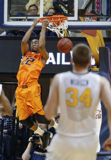 Oklahoma State's Markel Brown (22) dunks during the second half of an NCAA college basketball game in Morgantown, W.Va., on Saturday, Feb. 23, 2013. Oklahoma State defeated West Virginia 73-57. (AP Photo/David Smith) ORG XMIT: WVDS108
