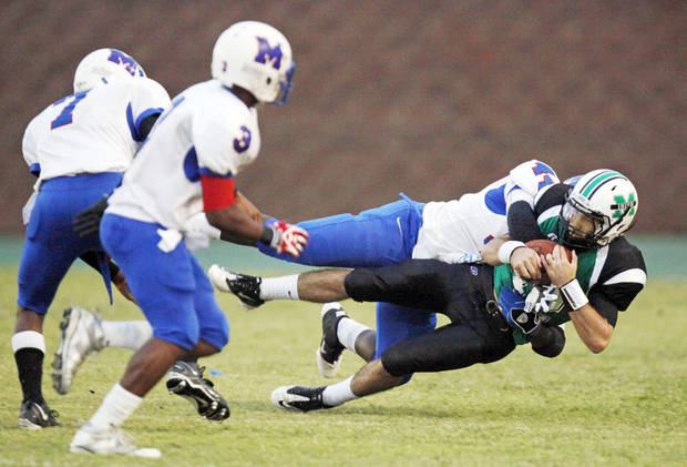 Millwood�s Larry Lambeth takes down Bishop McGuinness� Camden Tharp, bottom right, next to Malcom Scales, left, and Cameron Batson during a Sept. 16 game at Pribil Stadium.  Photo by Nate Billings, The Oklahoman
