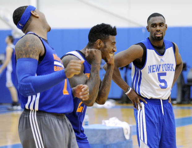 New York Knicks' Tim Hardaway, Jr. (5) looks on as Iman Shumpert and Carmelo Anthony, left, react to their shooting drill at the teams NBA basketball training camp Tuesday, Oct. 1, 2013, in Greenburgh, N.Y. (AP Photo/Bill Kostroun)