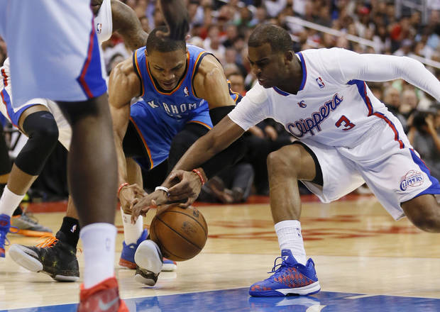 Oklahoma City Thunder guard Russell Westbrook, left, and Los Angeles Clippers guard Chris Paul reach for a loose ball during the first half of an NBA basketball game in Los Angeles, Wednesday, April 9, 2014. (AP Photo/Danny Moloshok)
