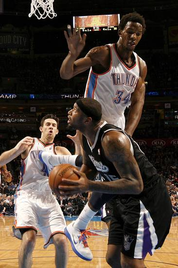 Oklahoma City's Hasheem Thabeet (34) defends Sacramento's DeMarcus Cousins (15) as Nick Collison (4) watches during an NBA basketball game between the Oklahoma City Thunder and the Sacramento Kings at Chesapeake Energy Arena in Oklahoma City, Friday, Dec. 14, 2012. Photo by Bryan Terry, The Oklahoman