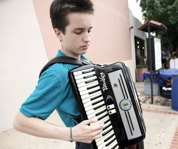 Timothy Granger, 14, plays songs with an accordion on the sidewalk for tips at the Paseo Arts Festival in Oklahoma City on May 25, 2013. Photo by KT King, The Oklahoman