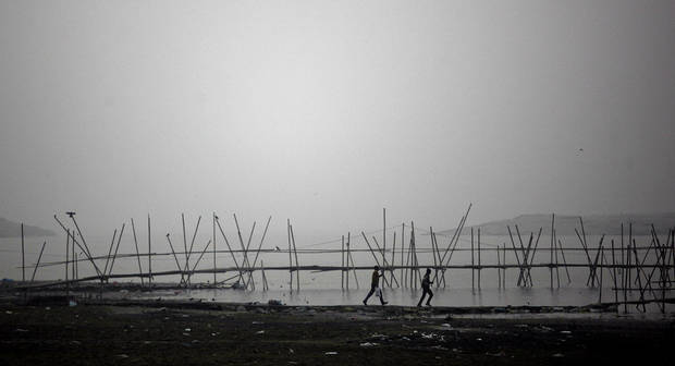 Indian commuters run to board a ferry on the banks of the River Brahmaputra in Gauhati, India, Tuesday, Jan. 8, 2013. North India continues to face below average weather conditions with dense fog affecting flights and trains. (AP Photo/Anupam Nath)
