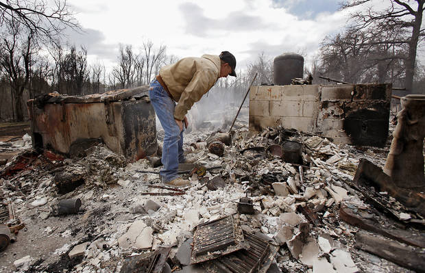 Kenneth Wertz digs through the remains of his house of more than 40 years as he looks for a few salvageable remains from the house that was destroyed by wildfires on Friday, April 10, 2009, in Choctaw, Okla.  Photo by Chris Landsberger, The Oklahoman