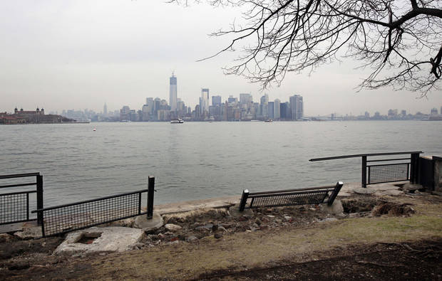 Manhattan island can be scene behind sections of a fence on Liberty Island, in New York,  Friday, Nov. 30, 2012. Tourists in New York will miss out for a while on one of the hallmarks of a visit to New York, seeing the Statue of Liberty up close. Though the statue itself survived Superstorm Sandy intact, damage to buildings and Liberty Island's power and heating systems means the island will remain closed for now, and authorities don't have an estimate on when it will reopen. (AP Photo/Richard Drew)