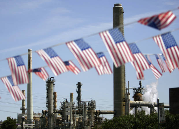 FILE - In this April 30, 2008 file photo, American flags are seen near the Shell refinery, in Martinez, Calif. On Weds., Nov. 14, 2012, California�s largest greenhouse gas emitters will for the first time begin buying permits in a landmark �cap-and-trade� system meant to control emissions of heat-trapping gases and spur investment in clean technologies. The program is a key part of California�s 2006 climate-change law, AB32, a suite of regulations that dictate standards for cleaner-burning fuels, more efficient automobiles and increased use of renewable energy. (AP Photo/Ben Margot, File)