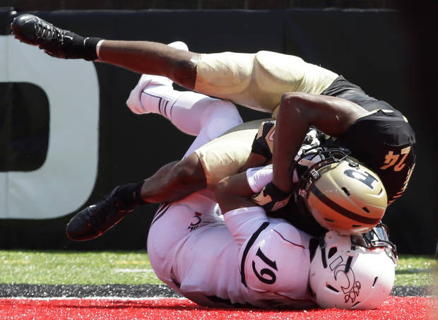 Purdue cornerback Frankie Williams (24) intercepts a pass  in the end zone intended for Cincinnati receiver Shaq Washington (19) during the second half of an NCAA college football game, Saturday, Aug. 31, 2013, in Cincinnati. Cincinnati won 42-7. (AP Photo/Al Behrman)