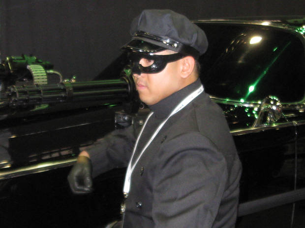 A performer portrays Kato with The Black Beauty car at Comic-Con International.