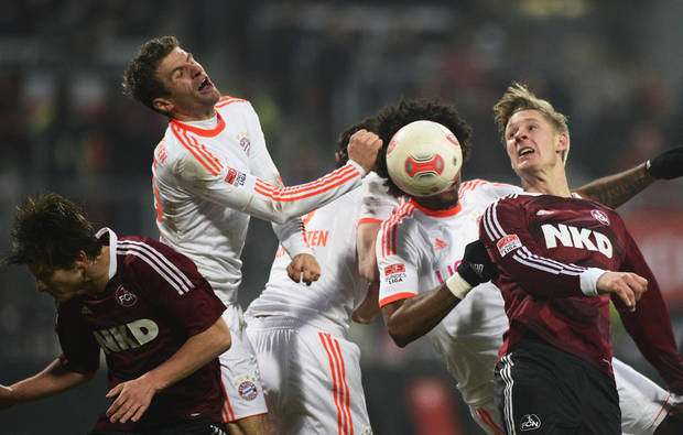 Munich's Thomas Mueller, second left, and Dante, second right, challenge with Nuremberg's Sebastian Polter , right, during the German Bundesliga soccer match between 1. FC Nuremberg and FC Bayern Munich in Nuremberg, southern Germany, Saturday Nov. 17, 2012. (AP Photo/dapd/Sebastian Widmann)