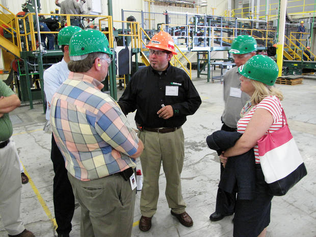 Jay Kreft of Malarkey Roofing Products, center, leads one of several tour groups through the plant at its grand opening Thursday at 3400 S Council Road. <strong>Richard Mize - The Oklahoman</strong>