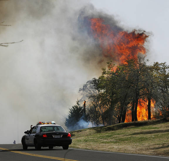 Trees burst into flames as wildfires march across eastern Oklahoma County  Thursday, April 9, 2009.  A Midwest City police car blocks traffic on Westminster between SE 15 and SE 29. Photo by Jim Beckel, The Oklahoman