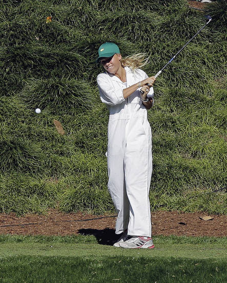 Tennis player Caroline Wozniacki tees off on the ninth hole during the par three competition before the Masters golf tournament Wednesday, April 10, 2013, in Augusta, Ga. Wozniacki was caddying for boyfriend Rory McIlroy, of Northern Ireland. (AP Photo/David J. Phillip)