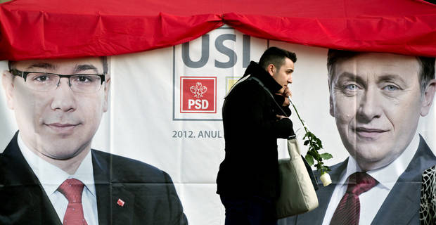 A man walks past a large electoral poster of the ruling Social Liberal Union in Bucharest, Romania, Wednesday, Dec. 5, 2012. Romania will hold parliamentary elections on Dec. 9, 2012. (AP Photo/Vadim Ghirda)