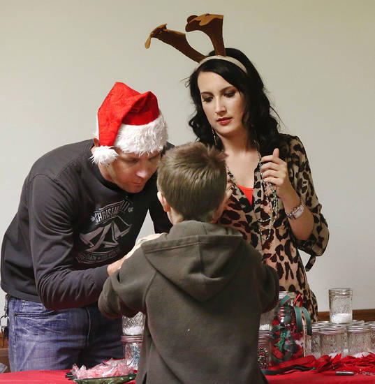 Eric Mackey, left, and Natalie Hancock, volunteers from Designer�s Brew Interior Design Studio, help fourth-grader Devven make a Christmas snow globe.